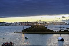 Sunset against the light with the Coruna sky line in the backgro. Und with people fishing in a small port and anchored boats nearby Stock Images
