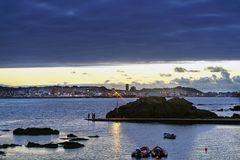 Sunset against the light with the Coruna sky line in the backgro. Und with people fishing in a small port and anchored boats nearby Royalty Free Stock Photography