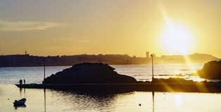 Sunset against the light with the Coruna sky line in the backgro. Und and people fishing in a small harbor Royalty Free Stock Photo