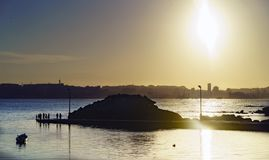 Sunset against the light with the Coruna sky line in the backgro. Und and people fishing in a small harbor Royalty Free Stock Photos