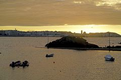 Sunset against the light with the Coruna sky line in the backgro. Und with people fishing in a small port and anchored boats nearby Royalty Free Stock Photo