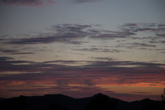 Sunset. Against a mountain with clouds royalty free stock images