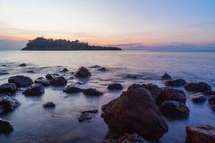 Sunset againt rock sea beach Stock Photos