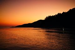 Sunset at Agnontas beach, Skopelos, Greece. Sunset on Skopelos just before dark with orange colored sky royalty free stock photo