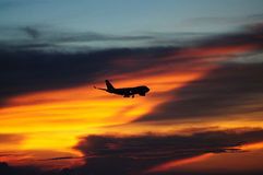 Sunset with airplane. Hong Kong, sunset on Airport seaside, airplane cross the sky royalty free stock image