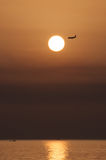 Sunset with airplane. Sunset and airplane in landing over the sea Stock Photos