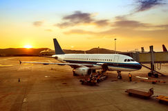 Sunset in the airport. Airplane near the terminal in an airport at the sunset Royalty Free Stock Image