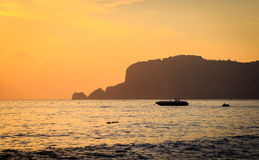 Sunset at Alanya coast. Sunset in Alanya, Turkey. Beautiful rocks and boat against colorful sky Stock Images