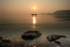 Sunset in Alicante Bay. Sailing boat anchored in Alicante Beach stock photography