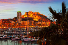 Sunset in Alicante, Spain. View of harbour with yachts against Castle on mount in background during sunset. Alicante, Spain Stock Photos
