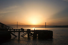 Sunset at Almada Quay and 25 de Abril Bridge in Lisbon Stock Images