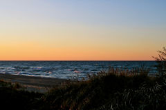 Sunset along beautiful Lake Michigan beach with view of Chicago skyline in far background Royalty Free Stock Images