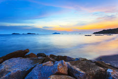 Sunset along the coast with sea stones background Stock Photography
