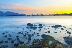 Sunset along coast with sea stones Stock Photo