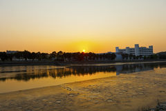 Sunset along river at factories Stock Image