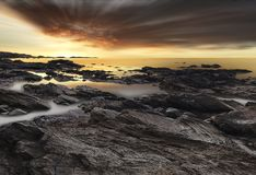 Sunset along a rocky shore in Philippines Stock Photography