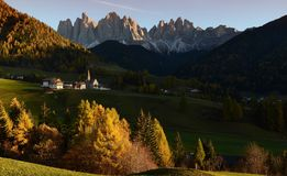 Sunset on The Alpine Village of Santa Magdalena in Val di Funes with the dolomitic group of the Odle on the background. The Alpine Village of Santa Magdalena in Royalty Free Stock Photography