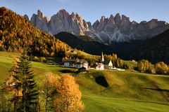 Sunset on The Alpine Village of Santa Magdalena in Val di Funes with the dolomitic group of the Odle on the background. The Alpine Village of Santa Magdalena in Stock Image
