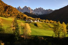 Sunset on The Alpine Village of Santa Magdalena in Val di Funes with the dolomitic group of the Odle on the background. The Alpine Village of Santa Magdalena in Stock Photo