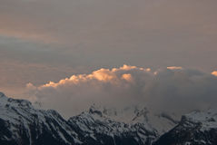 The sunset in the Alps Mountains. The Alps are one of the great mountain range systems of Europe stretching approximately 1,200 kilometres (750 mi) across eight Stock Photos