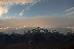 The sunset in the Alps Mountains. The Alps are one of the great mountain range systems of Europe stretching approximately 1,200 kilometres (750 mi) across eight Stock Photo