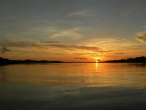 Sunset on the amazon river. Symmetry water and sky with scenic sunset on the amazon river, with orange clouds reflected in water stock images