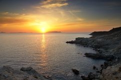 Sunset in Ampeli. Beautiful sunset near the beach Ampeli, Folegandros. In the background the sun sets on the island of Milos Stock Image