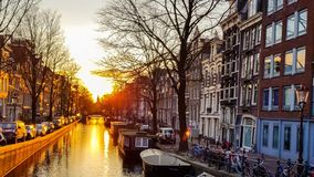 Sunset on the Amsterdam canal. Sunset reflected in the water of the Amsterdam canal against the background of beautiful houses, trees with parked boats, bicycles stock footage