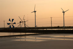 Sunset at ancient and new wind mill use for move the sea water i Royalty Free Stock Photography