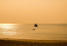Sunset by The Andaman Sea. Fishing boats pull their nets. Silhouette boat in the sunlight Royalty Free Stock Photography