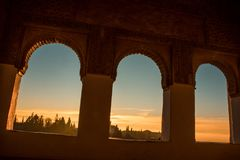 Sunset from Arabian windows. Arc shaped windows. And engraved on the wall Royalty Free Stock Images