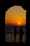 Sunset Arch. Silhouette stone archway with people at sunset and sea backdrop Royalty Free Stock Photos