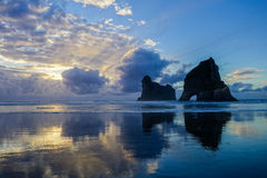 Sunset at Archway Islands. The sun sets at Wharariki Beach with a beautiful view on the Archway Islands Royalty Free Stock Photos