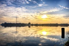 Sunset as seen in the edge of large pond. There is also a reflection of houses, sun, cloud, tree and communication tower Royalty Free Stock Photography