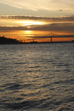 Sunset in Astoria OR. A beautiful sunset in Astoria Oregon, the bridge is visible and a large cargo ship approaching through the bridge is seen in a distance Royalty Free Stock Image