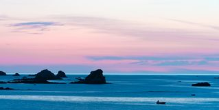 Free Sunset At The Beach With A Calm Ocean And Rocks And Reefs Under A Lilac Purple Sky Stock Photos - 160006813