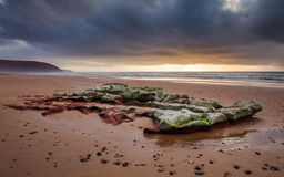 Sunset on the Atlantic coast overlooking a huge beautiful boulder under storm clouds Stock Photo