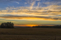Sunset in the autumn field. Beautiful evening in the autumn field after harvest Royalty Free Stock Photo