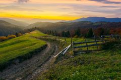 Sunset in autumn mountains. Winding country road through grassy rural hill. wooden fence along the path. trees in fall foliage. distant ridge in evening haze royalty free stock photo