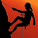 Sunset Back Abseiling Lady. Sunset Back Isolated Image of a Female Abseiler Climbing a Rock Face Stock Image
