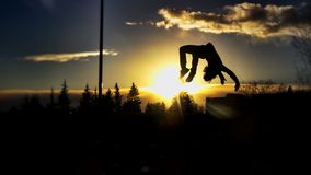 Sunset Backflip. A back flip silhouette on a winter sunset background Royalty Free Stock Image