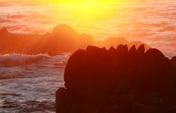 Sunset background of waves crashing on rocky coastline, California, USA. Dramatic background of ocean at dusk on Asilomar State Marine Reserve, Pacific Grove Royalty Free Stock Photography