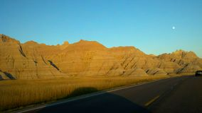 Sunset in the Badlands with moonrise. Setting sun in the Badlands while moon rises in the background stock photos