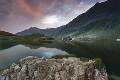 Sunset at Balea Lake. Lodge cabin on beautiful location Stock Image