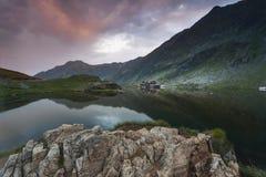 Sunset at Balea Lake. Lodge cabin on beautiful location Stock Image