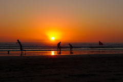 Sunset at Bali. People playing in the sunset light at Kuta Beach, Bali stock photos
