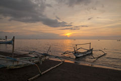 Sunset in Bali Indonesia. A typical sunset in Bali Indonesia.  There is old primitives fisherman boats Royalty Free Stock Photography