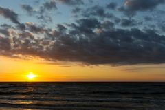 Sunset on the Baltic Sea. In Kolobrzeg. Dark clouds in the sky and very dark sea waters show that the night is approaching Stock Photography