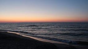 Sunset on Baltic Sea. Waves on seashore in evening