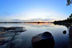 Sunset at Baltic sea. Wideangle landscape photo from Seurasaari, Helsinki. Sunset and mirror calm sea with colored sky with some clouds. Big rock gives distance Stock Photos